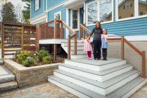 mother standing with two young daughters on renovated porch on blue house
