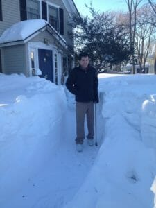 Max with cane between snow banks.