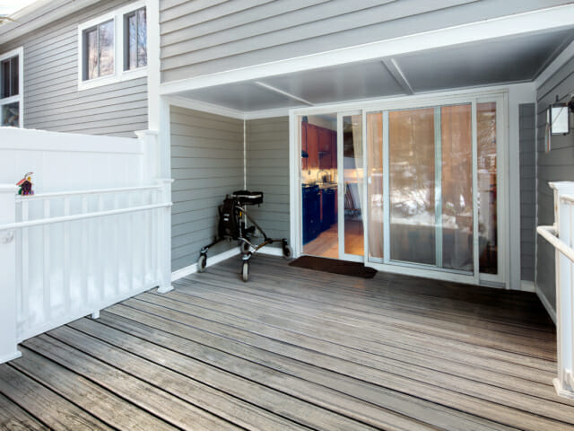 view of the exterior porch looking into the kitchen. Abbi's walker is beside the slider door.