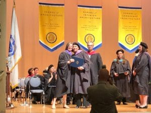 graduate in cap and gown posing with dean on stage